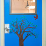 Room 600's door with bird flying from tree